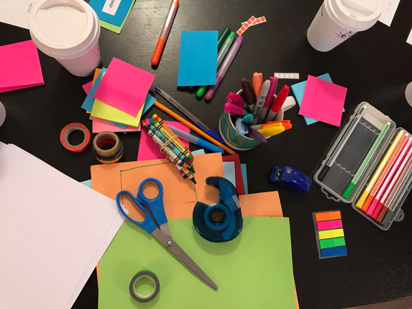 Messy desk with paper, scissors, crayons, markers, tape and more.