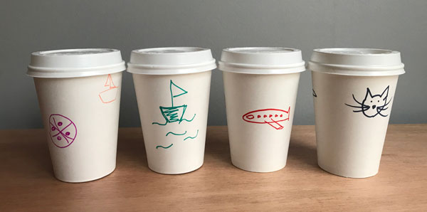 Blank to-go cups with drawings by participants: boats, cats, airplane.