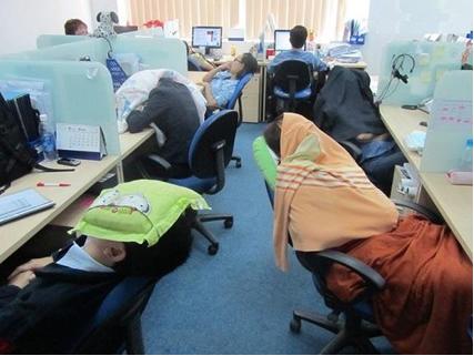 Photo d'employés faisant une sieste dans un open-space.