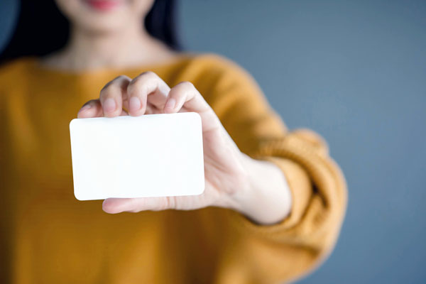 Person holding a blank business card.