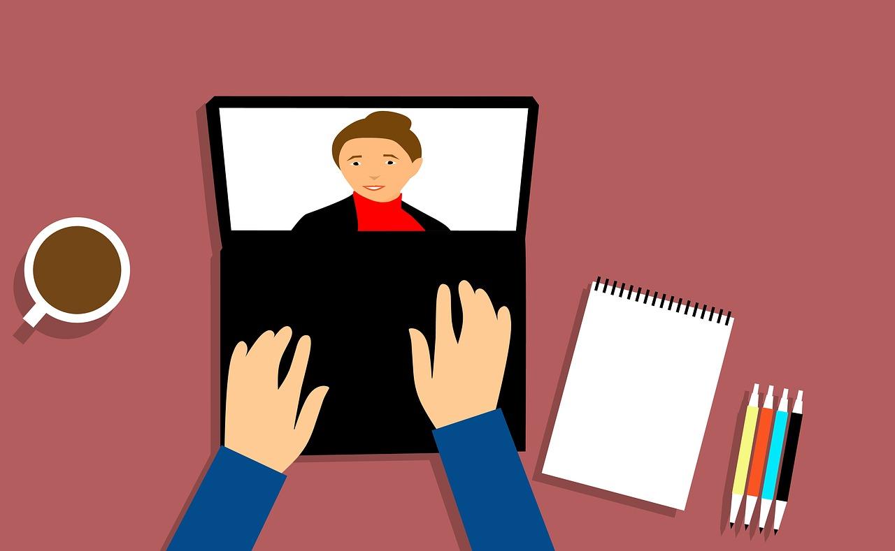 ordinateur vu de haut avec des mains dessus. Sur l'écran, on voit l'image d'une personne.