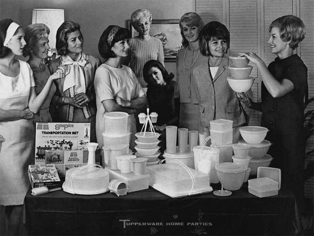 Groupe de femmes réunies pour une réunion Tupperware, où l'une d'entre elles présente les produits de la marque.
