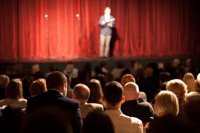 Comédien stand-up en train de se produire sur la scène d'un théâtre devant un public