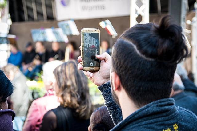 Jeune homme filmant avec son smartphone lors d'un événement
