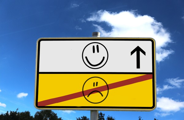 A road sign with a happy face and a sad face