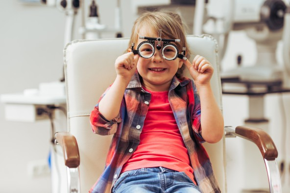A smiling child sits on a chair in an optometrist's office holding an eye testing tool in front of her eyes.
