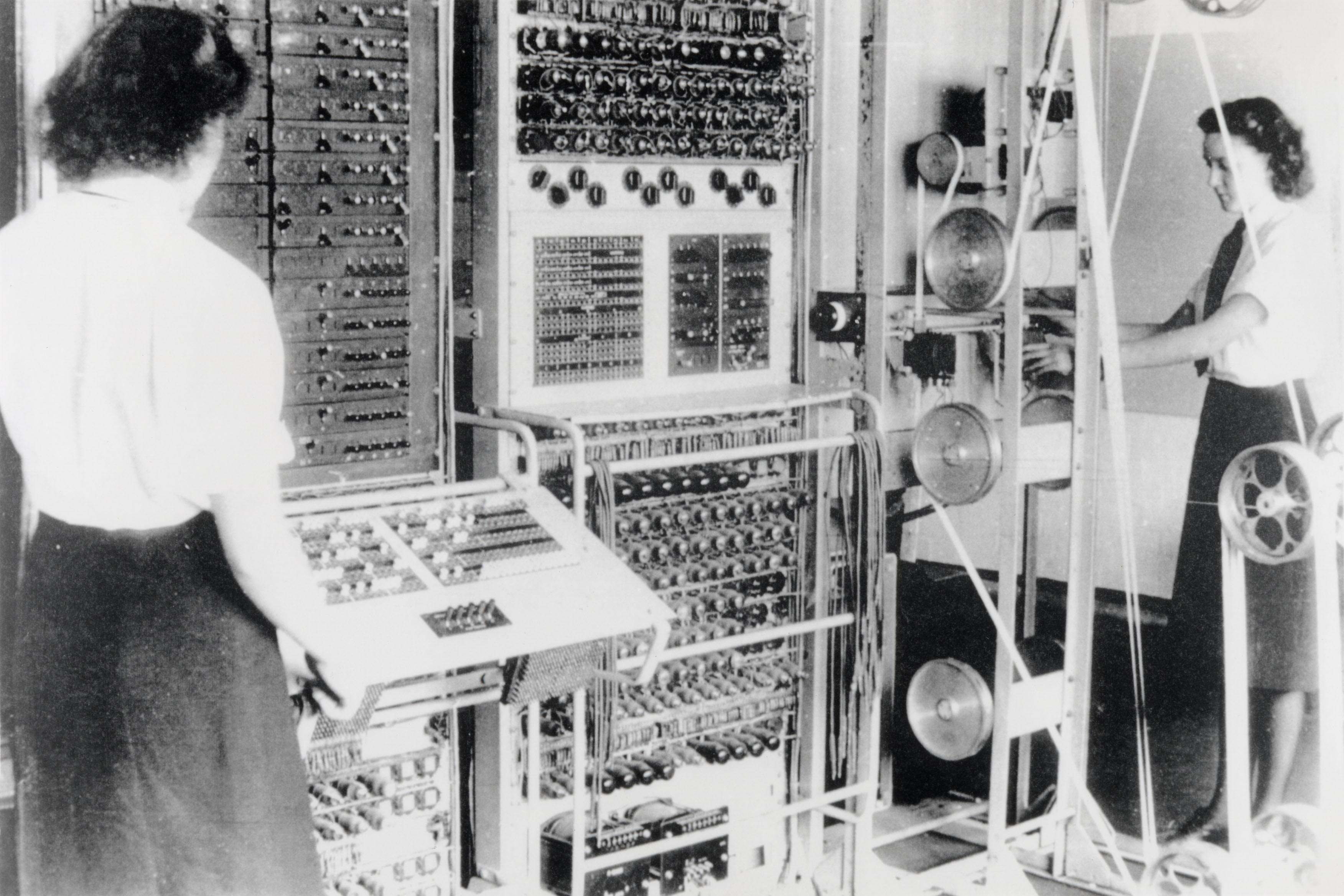Deux femmes en train de manipuler un très vieil ordinateur.