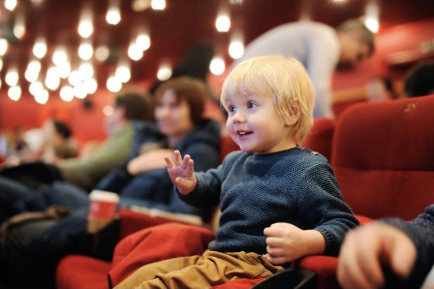 Un enfant sur un grand siège rouge d'une salle de spectacle