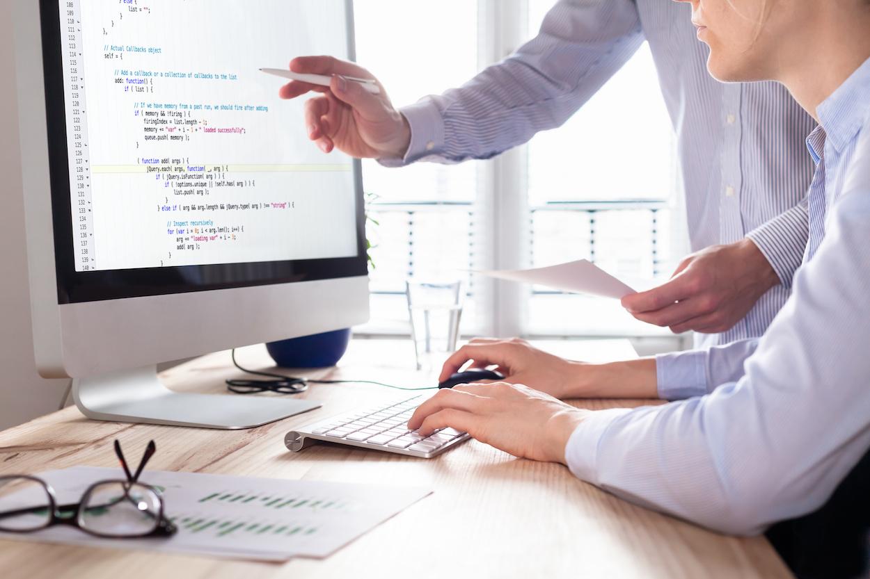 Photo d'une personne qui code et qui se fait aider par une autre